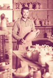 Happy man potter holding ceramic vessels. In atelier royalty free stock photos