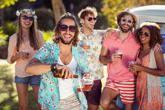 Happy man pouring beer in a glass while his friends standing in background Stock Images