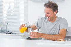 Happy man pouring orange juice for breakfast Royalty Free Stock Photography