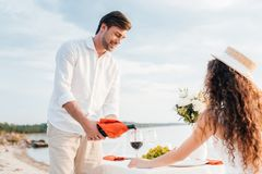 Happy man pouring red wine into glass for woman on romantic date. On beach stock photos