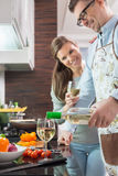 Happy man pouring white wine in glass while cooking with woman at kitchen Stock Image