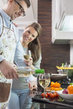 Happy man pouring white wine in glass while cooking with woman at kitchen Stock Photos