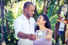 Happy man with pregnant wife holding sonogram. Happy men with pregnant wife holding sonogram against white background Royalty Free Stock Photo