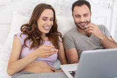 Happy man and pregnant woman watching movie. Funny comedy. Positive men and pregnant women regarding film and laughing Stock Images