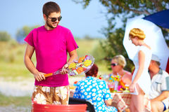 Happy man prepares food on the grill, family picnic Stock Photos