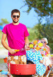 Happy man prepares food on the grill, family picnic Royalty Free Stock Images