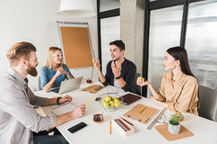 Happy man presenting idea to co-workers stock photos