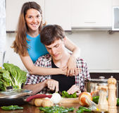 Happy man and pretty woman cooking together Stock Images