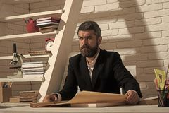 Happy man. Professor with confident face expression sits at desk. And reads map. Classic education and knowledge concept. Man with beard on white brick wall royalty free stock images