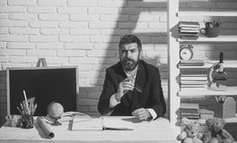 Happy man. Professor with thoughtful face expression sits at desk. Teacher and school supplies in classroom. Education and knowledge concept. Man with beard on royalty free stock image