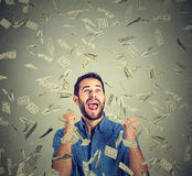 Happy man pumping fists celebrates success screaming under money rain Royalty Free Stock Photos