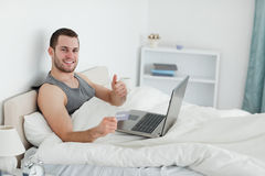 Happy man purchasing online with thumb up Stock Image