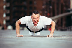 Happy Man push ups outdoors during fitness training. Royalty Free Stock Photos