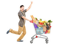 Happy man pushing a shopping cart stock photo