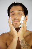 Happy man putting shaving cream on his face Royalty Free Stock Photography