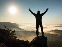 Happy man with raised arms gesture triumph  on exposed cliff. Satisfy hiker Royalty Free Stock Images
