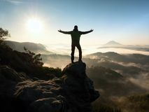 Happy man with raised arms gesture triumph  on exposed cliff. Satisfy hiker Stock Image
