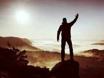 Happy man with raised arms gesture triumph  on exposed cliff. Satisfy hiker Stock Photos