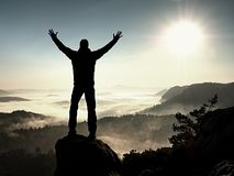 Happy man with raised arms gesture triumph  on exposed cliff. Satisfy hiker Royalty Free Stock Photos