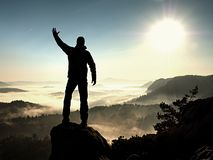 Happy man with raised arms gesture triumph  on exposed cliff. Satisfy hiker Royalty Free Stock Photo