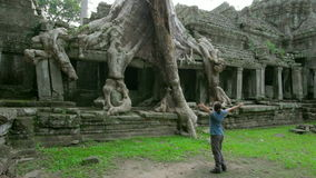 Happy man raising arms in mysterious preah khan temple, angkor stock footage