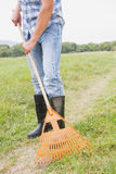 Happy man raking his farm Stock Image