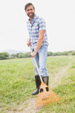 Happy man raking his farm Royalty Free Stock Photography