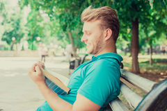 Happy man reading a book funny story in a park on summer sunny day Royalty Free Stock Photography