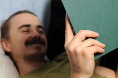 Happy man reading book lying on coach Royalty Free Stock Photography