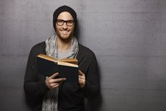 Happy man reading book. Happy urban style young man standing against grey wall, smiling, reading book, looking at camera Royalty Free Stock Images