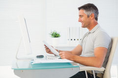 Happy man reading document at desk Royalty Free Stock Photography