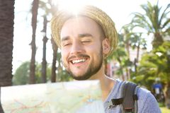 Happy man reading map while on vacation Royalty Free Stock Images