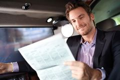 Happy man reading news in luxury car Stock Image