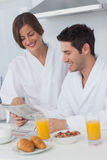 Happy man reading a newspaper while having breakfast Royalty Free Stock Images