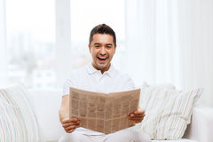 Happy man reading newspaper and laughing at home Royalty Free Stock Photography