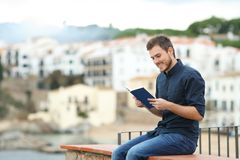 Happy man reading a paper book on vacation royalty free stock photos