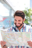 Happy man reading road map in city Royalty Free Stock Images
