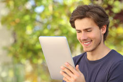 Happy man reading a tablet reader outdoors. With a green background royalty free stock photo