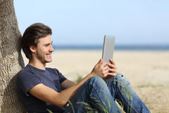 Happy man reading a tablet reader sitting on the beach Royalty Free Stock Photo