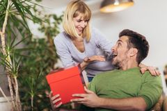 Man receiving a present from his girlfriend while sitting on the sofa. Happy men receiving a present from his girlfriend while sitting on the sofa stock photos