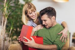 Man receiving a present from his girlfriend while sitting on the sofa. Happy men receiving a present from his girlfriend while sitting on the sofa stock photography