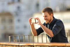 Happy man recording videos with smart phone. With a town in the background royalty free stock photos