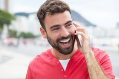Happy man with red shirt at cellphone in the city Stock Image