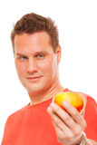 Happy man in red shirt holding apple. Diet health care healthy nutrition. Stock Photography
