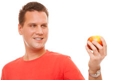 Happy man in red shirt holding apple. Diet health care healthy nutrition. Royalty Free Stock Photos