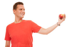 Happy man in red shirt holding apple. Diet health care healthy nutrition. Royalty Free Stock Images