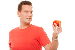 Happy man in red shirt holding apple. Diet health care healthy nutrition. Royalty Free Stock Photography