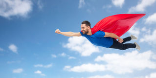 Happy man in red superhero cape flying on air Royalty Free Stock Photography