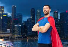 Happy man in red superhero cape over night city. Power and people concept - happy man in red superhero cape over night singapore city skyscrapers background Stock Photos