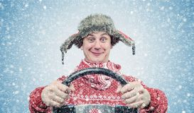Happy man in red sweater and hat with a steering wheel, snow blizzard. Concept car driver.  Stock Photography
